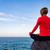 woman meditating in yoga pose ocean view stock photo © blasbike