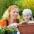young woman and little girl gardening in spring planting flower seedlings smiling mother and her h stock photo © brozova