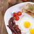 fried egg and bacon on a plate with spices and vegetables stock photo © brunoweltmann