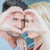 couple looking through hands making heart shape stock photo © dash