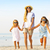 happy young family having fun running on beach at sunset family stock photo © dashapetrenko