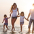 happy young family having fun running on beach at sunset stock photo © dashapetrenko