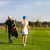 couple playing golf on a golf course walking to the next hole stock photo © dashapetrenko