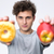 casual young man holding apple and donut stock photo © deandrobot