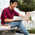 cheerful asian young man sitting and using laptop outdoors stock photo © deandrobot