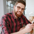 young bearded man checking his newsfeed on social media stock photo © deandrobot