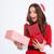 surprised female in santa claus costume looking inside present box stock photo © deandrobot