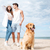 couple and their dog standing on the beach stock photo © deandrobot