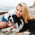 cheerful woman sitting and hugging her dog on the beach stock photo © deandrobot