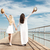 two attractive young women with raised hands walking on pier stock photo © deandrobot