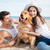 smiling couple in love sitting on the beach with dog stock photo © deandrobot