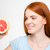 smiling young happy redhead female looking on half of grapefruit stock photo © deandrobot