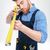 concentrated bearded young worker in overalls using measuring tape stock photo © deandrobot