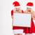 sisters twins in santa dresses and hats holding blank board stock photo © deandrobot