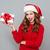 woman in santas hat keeps christmas gift stock photo © deandrobot