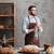 Happy bearded man baker standing near a lot of bread. stock photo © deandrobot