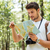 man with photo camera standing and using map in forest stock photo © deandrobot