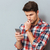 pensive young man in checkered shirt using mobile phone stock photo © deandrobot