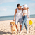 beautiful couple walking on the sea shore with dog stock photo © deandrobot