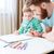 Handsome man and his little son drawing together at home stock photo © deandrobot