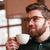 smiling bearded young man drinking coffee stock photo © deandrobot