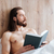 pensive bearded young man reading book and thinking in bed stock photo © deandrobot
