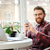 happy bearded young man using mobile phone and laptop computer stock photo © deandrobot