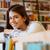 gelukkig · glimlachend · vrouwelijke · student · boekenplank - stockfoto © deandrobot