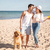 couple walking on the sea shore with dog stock photo © deandrobot