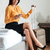 cheerful businesswoman looking at mobile phone while sitting on bed stock photo © deandrobot