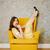 függőleges · kép · meglepődött · nő · fotel · citromsárga - stock fotó © deandrobot