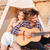 man playing guitar for his girlfriend sitting at camping tent stock photo © deandrobot