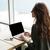 achteraanzicht · zakenvrouw · laptop · glimlachend · vergadering · tabel - stockfoto © deandrobot