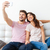 beautiful young couple is making selfie using a smartphone stock photo © deandrobot