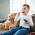 Little happy boy sitting on sofa with teddy bear stock photo © deandrobot
