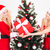two sisters twins holding one gift near christmas tree stock photo © deandrobot
