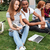 happy people reading book and using laptop on lawn outdoors stock photo © deandrobot