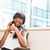 smiling businesswoman talking on the phone in office stock photo © deandrobot