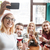 Cheerful friends sitting in cafe and make selfie by phone. stock photo © deandrobot