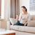 女性 · 座って · ソファ · スマートフォン · 笑顔の女性 · ホーム - ストックフォト © deandrobot