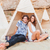 happy young couple sitting in teepee on the beach stock photo © deandrobot
