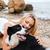 cheerful woman hugging her dog on the beach in summer stock photo © deandrobot