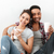 cheerful multiethnic young couple drinking coffee and hugging stock photo © deandrobot