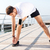 young sportsman stretching legs during workout on pier stock photo © deandrobot