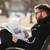 Man in glasses sitting and reading newspaper at the city stock photo © deandrobot