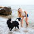 cheerful woman playing with dog on the seaside stock photo © deandrobot