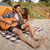 young happy couple playing guitar while sitting at the beach stock photo © deandrobot