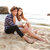 young beautiful happy couple embracing while sitting at the beach stock photo © deandrobot