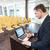 geconcentreerde · zakenman · met · behulp · van · laptop · permanente · kantoor · internet - stockfoto © deandrobot