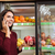 happy young woman talking on cell phone and buying pomegranate stock photo © deandrobot